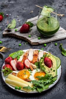 Koncepcja diety ketogenicznej o niskiej zawartości węglowodanów, jajko sadzone, awokado, truskawka, grillowany filet z kurczaka, ser, orzechy i rukola. koktajl detox, świeża zieleń, koncepcja zdrowej żywności, widok z góry,