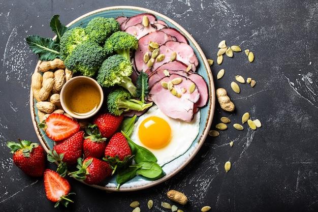 Koncepcja diety ketogenicznej o niskiej zawartości węglowodanów, widok z góry. talerz na kamiennym czarnym tle z keto żywności: jajko, mięso, oliwa z oliwek, brokuły, jagody, orzechy, nasiona, szpinak. zdrowe tłuszcze, czyste jedzenie na odchudzanie