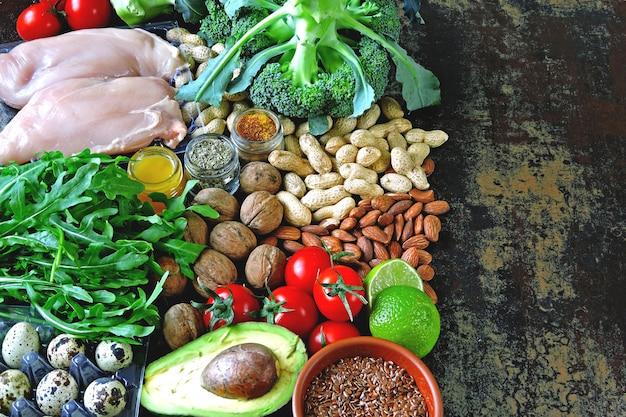 Koncepcja diety ketogenicznej. zestaw produktów diety ketonowej o niskiej zawartości węglowodanów. zielone warzywa, orzechy, filet z kurczaka, nasiona lnu, jaja przepiórcze, pomidory koktajlowe. koncepcja zdrowej żywności. dieta ketonowa.