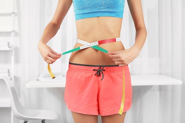 Koncepcja diety. kobieta z miarką w pokoju