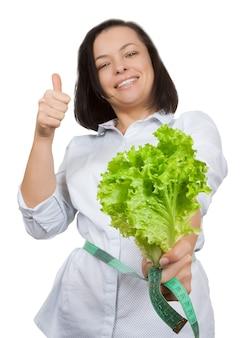 Koncepcja diety. młoda kobieta z sałatą mierząca talię miarką na białym tle
