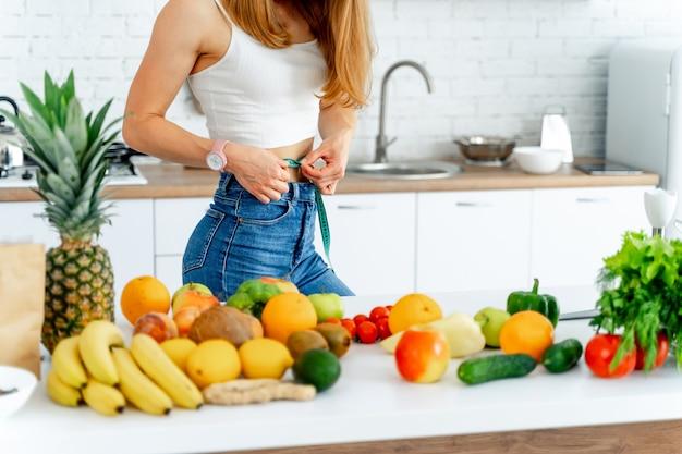 Koncepcja diety. piękna młoda kobieta w kuchni ze zdrową żywnością. miarka w pasie. owoce i warzywa