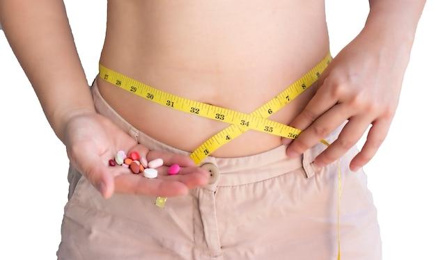 Koncepcja diety: szczupła z pigułkami, niebezpieczna dla zdrowia, lekarstw i miarki w dłoni kobiety.