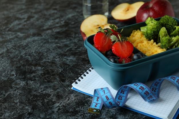 Koncepcja diety z pudełkiem na lunch na czarnym stole smokey