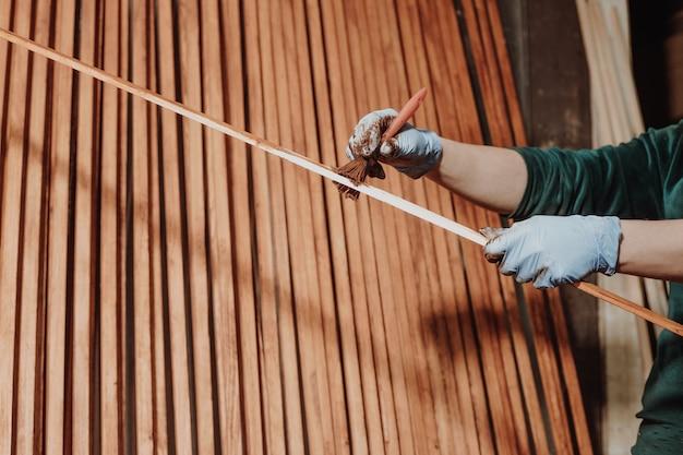 Koncepcja diy, kobieta malująca kawałki drewna dla niej nowe meble, gospodarstwo domowe