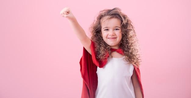 Koncepcja dla dzieci, uśmiechnięta dziewczyna gra superbohatera
