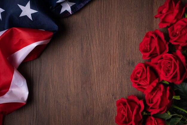 Koncepcja dnia niepodległości stanów zjednoczonych lub dnia pamięci. flaga narodowa i czerwona róża na tle ciemnego drewnianego stołu.