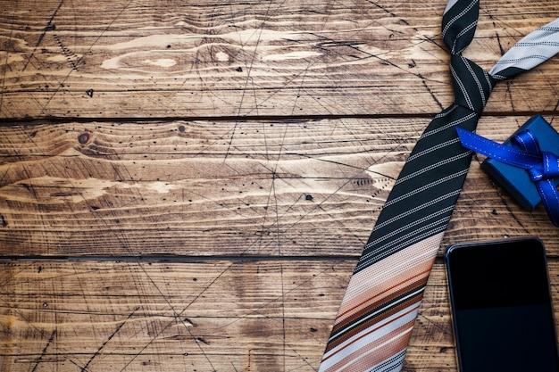 Koncepcja dnia ojca. pasiasty krawat i prezent na drewnianym tle z kopii przestrzenią.
