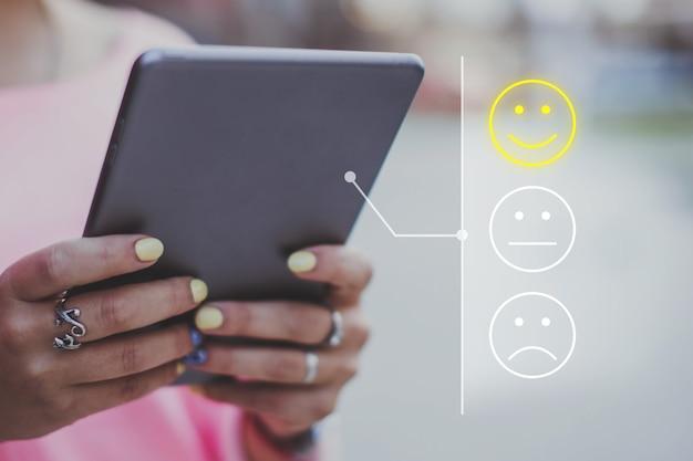 Koncepcja dobrego nastroju wykonana z emotikonów i oceny. dziewczyna stawia oceny w internecie za pomocą tabletu.