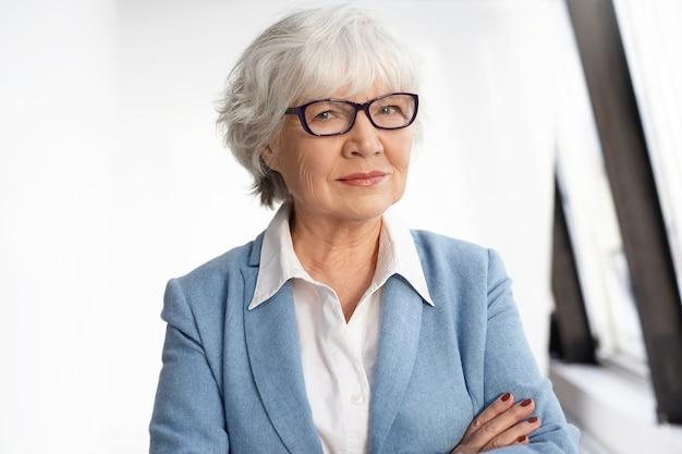 Koncepcja dojrzałości, wieku, doświadczenia i emerytury. pewna siebie, dojrzała prezeska ubrana w stylowe stroje wizytowe i okulary skrzyżowane na piersi. inteligentny starszy kaukaski kobieta pozowanie w pomieszczeniu