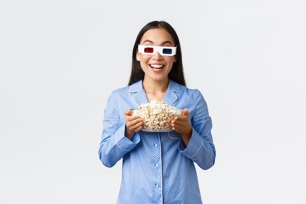 Koncepcja domowego wypoczynku, nocowania i snu. entuzjastyczna azjatka w piżamie i okularach 3d, trzymająca miskę popcornu i uśmiechnięta, rozbawiona oglądając premierę w telewizji, ciesząc się nocą filmową