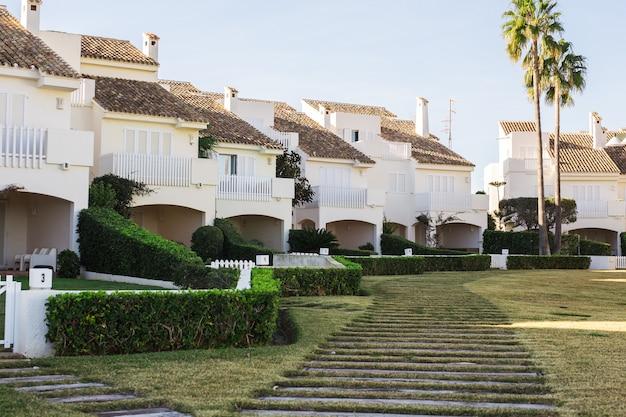 Koncepcja domu, budynku i architektury - ulica dużych domów podmiejskich latem.