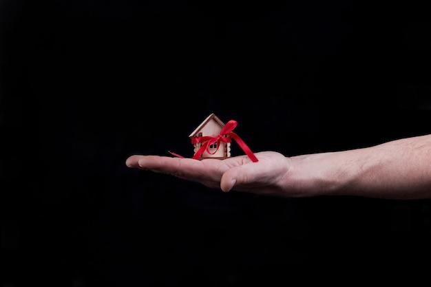Koncepcja domu hipotecznego z czerwoną wstążką pod ręką na czarnym tle