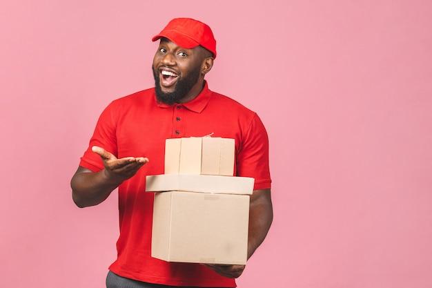 Koncepcja dostawy. afroamerykanin dostawy czarny człowiek przewożący paczkę na białym tle na różowym tle.
