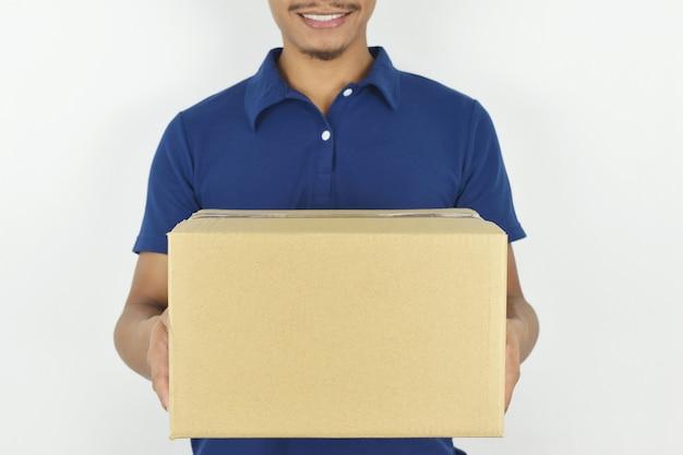 Koncepcja dostawy dostawca w niebieskim mundurze trzymającym pudełko na szarym tle