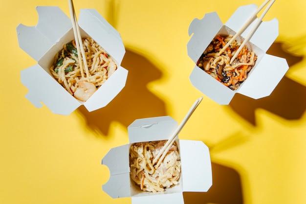 Koncepcja dostawy jedzenia na żółtym tle makaron w pudełkach