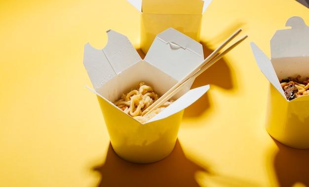 Koncepcja Dostawy Jedzenia Na żółtym Tle Makaron W Pudełkach Premium Zdjęcia