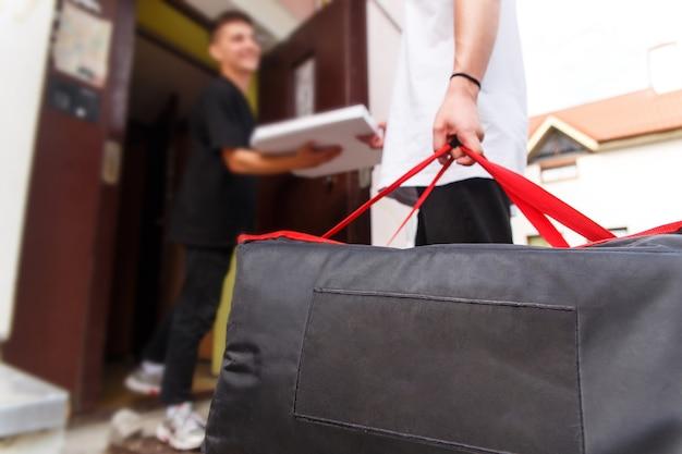 Koncepcja dostawy jedzenia, poczty i ludzi - mężczyzna dostarczający pizzę w termotorbie do domu klienta i wręczający ją klientowi