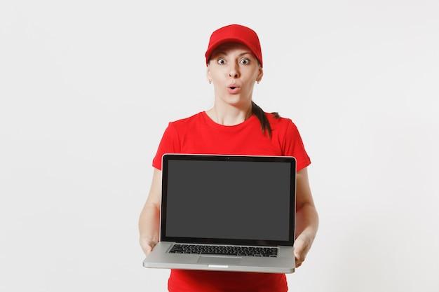 Koncepcja dostawy. kobieta w czerwonej czapce, t-shirt na białym tle. profesjonalna kobieta kaukaska pracuje jako kurier trzymając komputer pc z pustym pustym ekranem, aby skopiować miejsce na reklamę.