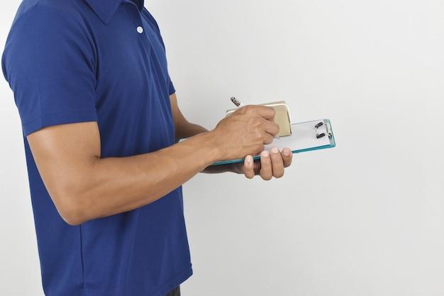 Koncepcja dostawy mężczyzna dostawy trzymający paczkę i piszący w schowku na szarym tle