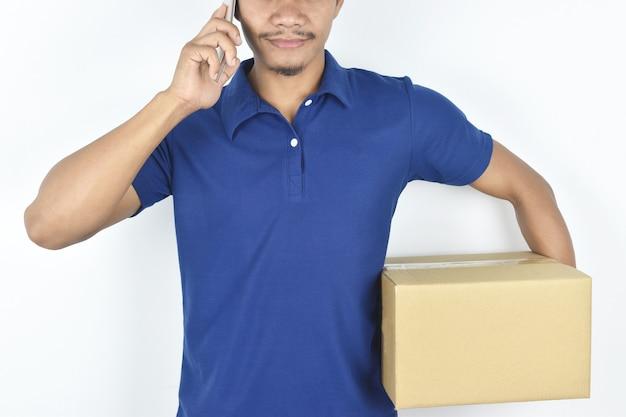 Koncepcja dostawy młody mężczyzna dostawy trzymający pudełko i pokazujący gesty, aby zadzwonić do klientów