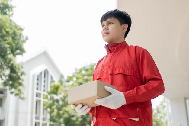 Koncepcja dostawy paczki listonosz w czerwonym mundurze i rękawiczkach niektórych firm logistycznych, który przekazuje paczkę klientowi podczas pandemii covid19.