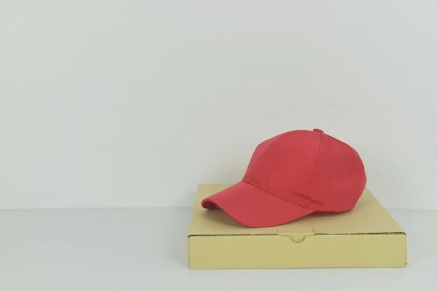 Koncepcja dostawy pizzy z czapką z daszkiem na białym