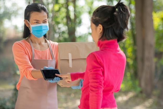 Koncepcja dostawy, poczty, ludzi i wysyłki. młoda kobieta zaloguj się cyfrowy telefon komórkowy po otrzymaniu przesyłki od kuriera w domu. od dostawcy podczas epidemii covid-19.