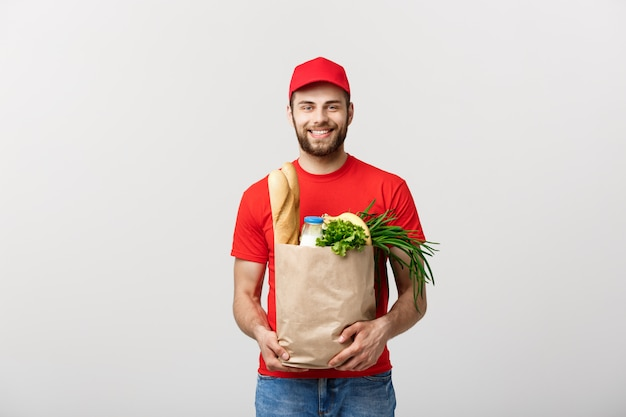 Koncepcja dostawy - przystojny mężczyzna dostawy cacasian niosący torbę z jedzeniem i piciem ze sklepu spożywczego. pojedynczo na szarym studio ścianie. kopiuj przestrzeń.