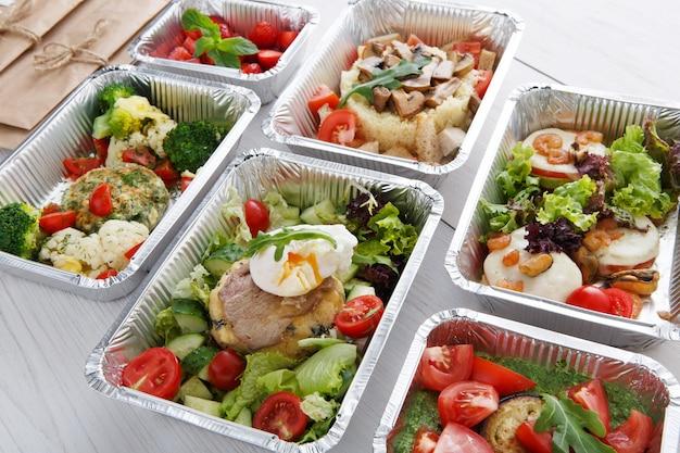 Koncepcja dostawy restauracji zdrowej żywności. zabierz posiłek. obiad w pudełkach foliowych. jajko w koszulce ze stekiem i innymi daniami na białym drewnie