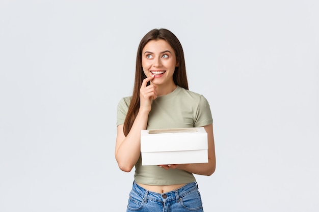 Koncepcja dostawy, stylu życia i żywności. marzycielska szczęśliwa stylowa kobieta patrząca w górę zamyślona, uśmiechnięta jak obrazowanie czegoś, trzymająca pudełko z deserami, pyszne jedzenie, stoisko białe tło.
