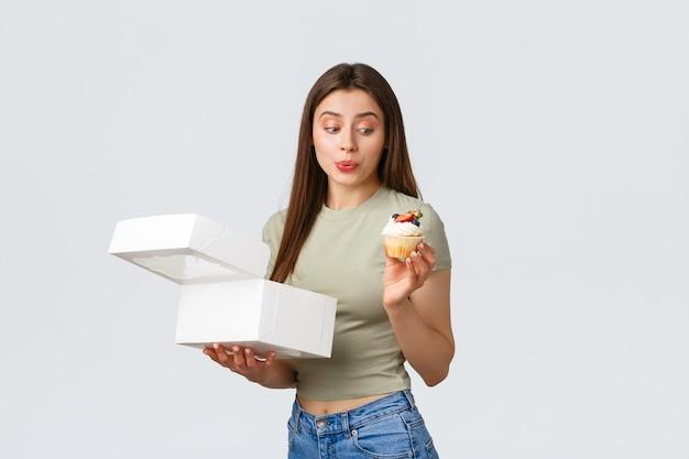Koncepcja dostawy, stylu życia i żywności. niemądra ładna kobieta otwiera pudełko deserów z cukierni lub piekarni, patrząc kusząco i z pożądaniem na pyszną słodką babeczkę, białe tło