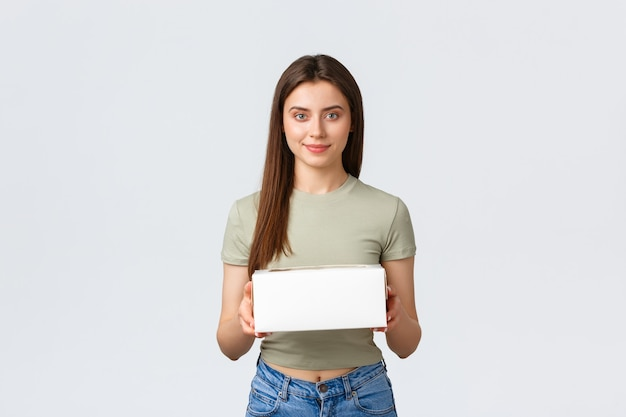 Koncepcja dostawy, stylu życia i żywności. stylowa młoda ładna kobieta trzyma pudełko z posypką, zamówienie deserów z ulubionej kawiarni. dziewczyna odbiera dostawę do domu z restauracji