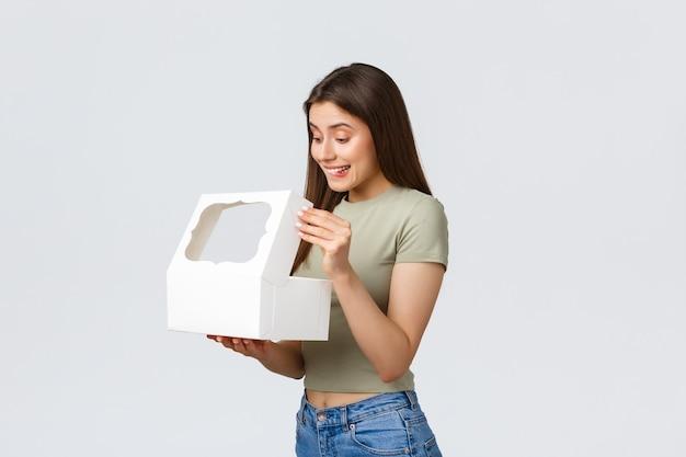 Koncepcja dostawy, stylu życia i żywności. uśmiechnięta szczęśliwa dziewczyna otwiera białe pudełko ze słodkimi pysznymi deserami, ciastami lub babeczkami zamówionymi w najlepszej cukierni, stojąc na białym tle.