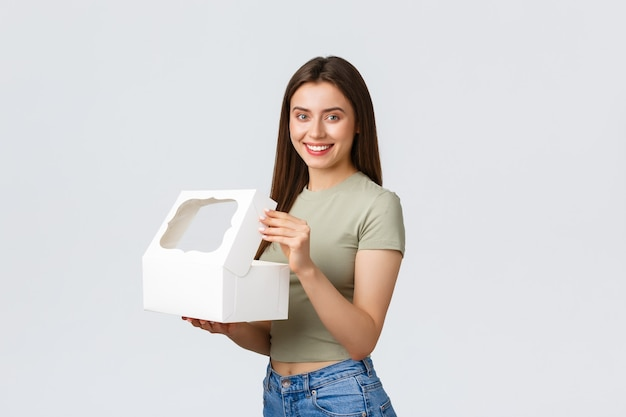 Koncepcja dostawy, stylu życia i żywności. wesoła młoda kobieta uśmiecha się do kamery po otwarciu pudełka z cukierni. klientka otrzymuje zamówienie z piekarni lub ulubionej kawiarni, delektując się deserami