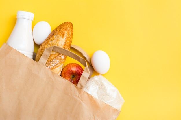 Koncepcja dostawy żywności. chleb, mleko, jajka, zboża i owoce w papierowej torbie na żółtym tle