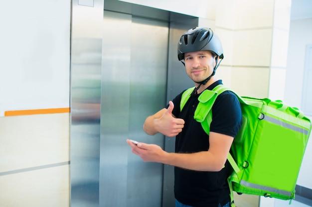 Koncepcja dostawy żywności. człowiek dostarczający jedzenie idzie windą, by znaleźć mieszkanie, które złożyło zamówienie. patrzy w kamerę i podnosi kciuk do góry.