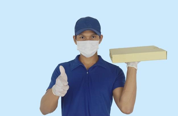 Koncepcja dostawy żywności dostawca w rękawiczkach z maską medyczną i trzymający pudełko po pizzy w dłoniach z kciukami do góry na niebiesko