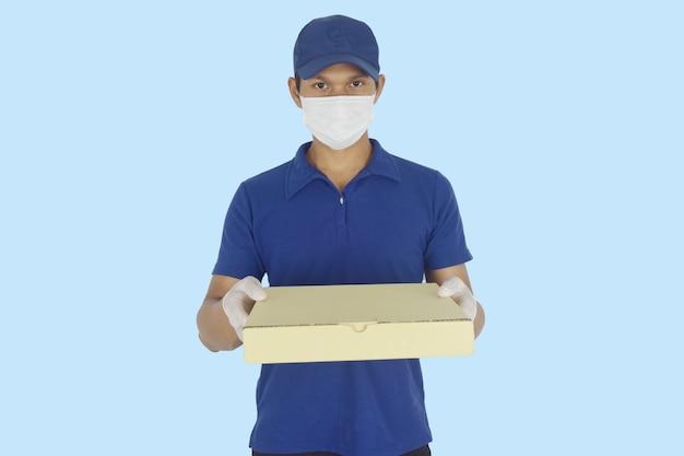 Koncepcja dostawy żywności dostawca w rękawiczkach z maską medyczną i trzymający pudełko po pizzy w rękach na niebiesko