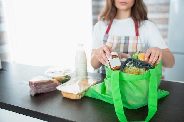 Koncepcja dostawy żywności. jest jedzenie z bliska. kobieta przygotowuje paczkę dla klienta.