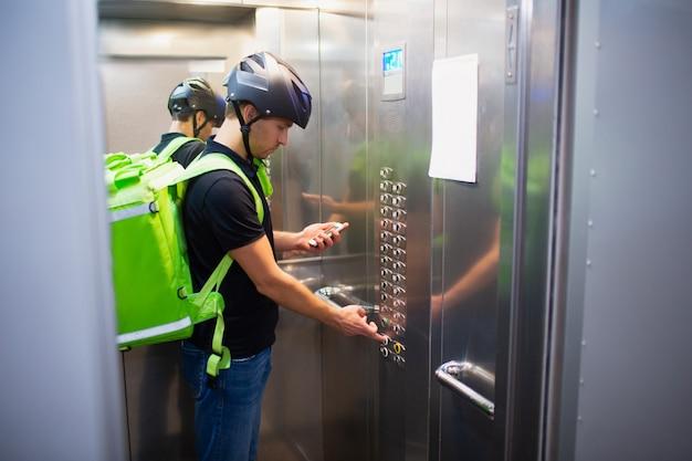 Koncepcja dostawy żywności. mężczyzna dostarczający jedzenie idzie windą, by znaleźć mieszkanie, które złożyło zamówienie.