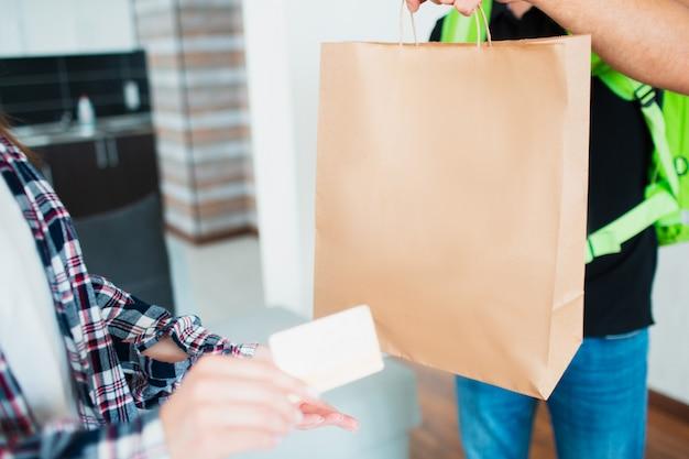Koncepcja dostawy żywności. mężczyzna dostawy żywności przyniósł jedzenie do domu młodej kobiety. ona chce zapłacić za zamówienie za pomocą karty kredytowej