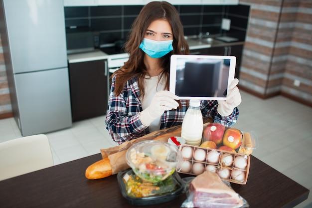 Koncepcja dostawy żywności. młoda kobieta w medycznej masce i gumowych rękawiczkach jednorazowych zamawia jedzenie za pomocą tabletu w domu. na stole jest mleko, sałatki w pudełkach, mięso, jedzenie, owoce, jajka, chleb.