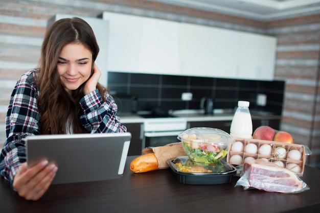 Koncepcja dostawy żywności. młoda kobieta zamawia jedzenie za pomocą laptopa w domu. na stole jest mleko, sałatki w pudełkach, mięso, jedzenie, owoce, jajka, chleb.
