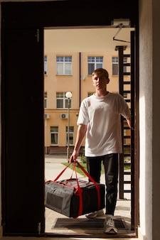 Koncepcja dostawy żywności, poczty i ludzi - mężczyzna dostarczający pizzę w termotorbie do domu klienta i wchodzi do wejścia