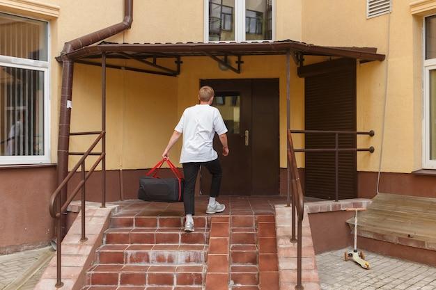 Koncepcja dostawy żywności, poczty i ludzi - mężczyzna dostarczający pizzę w termotorbie do domu klienta i wspina się po schodach na ganek domu