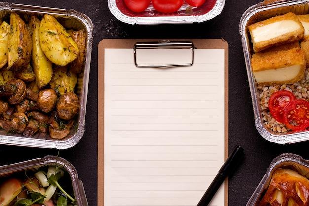 Koncepcja dostawy żywności. pusty formularz obok wegetariańskiego posiłku.