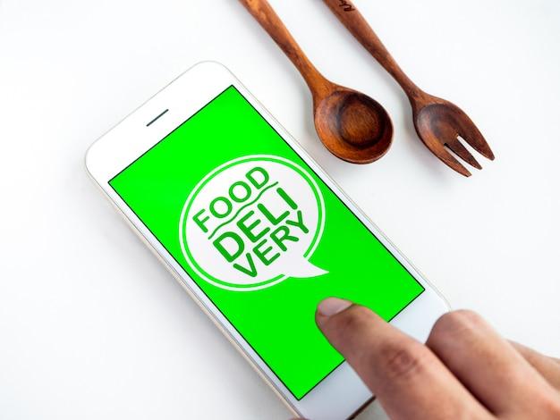 """Koncepcja dostawy żywności. słowa """"dostawa żywności"""" na ekranie smartfona. zamawianie jedzenia przez technologię smartfona."""