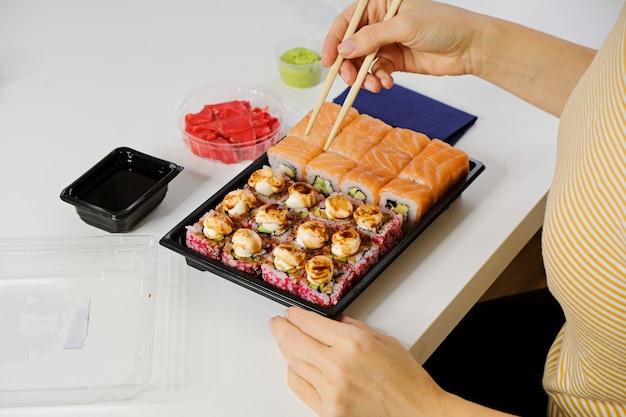 Koncepcja dostawy żywności sushi. kobieta jedząca philadelphia roll z plastikowej zastawy stołowej