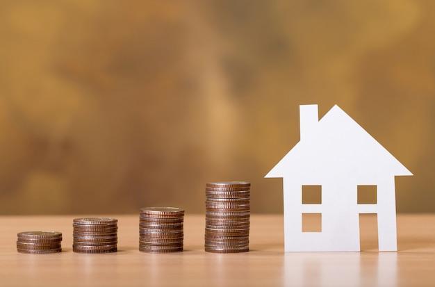 Koncepcja drabiny nieruchomości, domu z papieru i stosu monet do oszczędzania na zakup domu